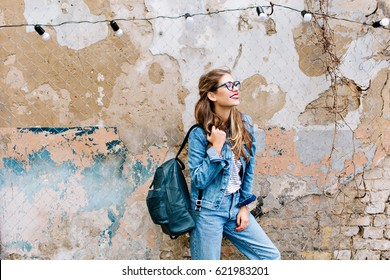 Stylish hipster girl in the retro jeans suit posing in front of the old brick wall. Trendy young woman with bag standing next to old building. Street fashion concept, wearing glasses