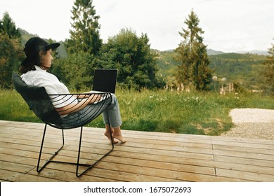 Stylish hipster girl sitting with laptop on terrace with view on woods. Young happy woman in hat using laptop, shopping or working online from home outdoors. Freelance and freelancer