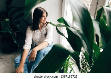 Stylish hipster girl sitting on floor and looking at white rustic window with green plants in modern cafe. Fashionable woman relaxing in soft light at wooden window and green leaves indoors