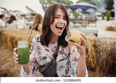Stylish hipster girl in sunglasses holding delicious vegan burger and smoothie in glass jar in hands at street food festival. Happy boho woman holding burger and drink in summer street