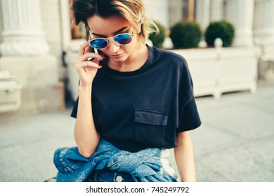 Stylish hipster girl in trendy sunglasses talking on mobile phone while strolling in street.Busy businesswoman dressed in black t-shirt communicating on modern smartphone device walking outdoors