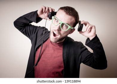 stylish hipster listening to music on gray background