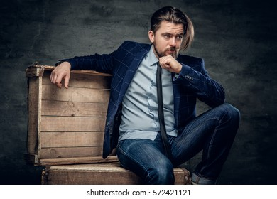 A stylish hipster man dressed in a jeans and bow tie sits on a wooden box.