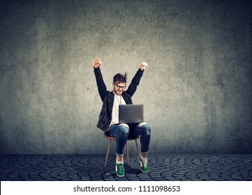 Stylish hipster man sitting on chair with laptop and celebrating victory looking excited with new achievement on gray
