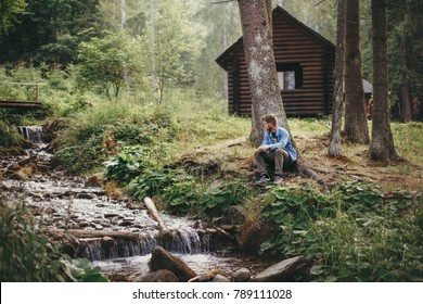stylish hipster man sitting and relaxing at wooden cabin in forest. guy exploring woods and river. space for text. travel and wanderlust concept.