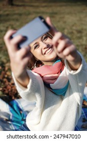 Stylish hipster smiling girl student with the mobile phone make selfie shot in the park outdoor