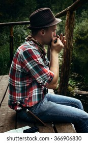 stylish hipster traveler playing harmonica at sunny lake in the forest in mountains