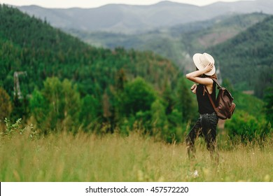 stylish hipster woman with backpack looking at  amazing woods and mountains in summer, travel concept, space for text