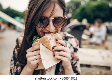 stylish hipster woman eating juicy burger. boho girl biting yummy cheeseburger, smiling at street food festival. summertime. summer vacation travel picnic. space for text