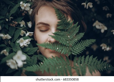 stylish hipster woman with fern leaf embracing. girl portrait with natural herb, boho sensual bride. romantic moment. rustic eco wedding concept. beautiful woman relaxing