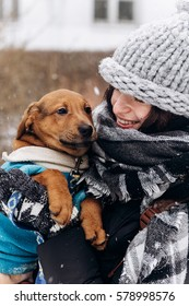 stylish hipster woman hugging and smiling cute puppy in snowy cold winter park and caressing. moments of true happiness. adoption concept. save animals