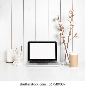 Stylish hipster workspace with open laptop computer, cup of coffee, painting brushes, candle and cotton plant branches in vase at home or studio.Desktop computer screen isolated. White desk mockup