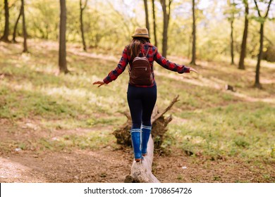 Stylish hipster young woman walking in the forest, carrying a backpack in the forest on sunset light in the spring season, looking at amazing woods, travel concept, space for text
