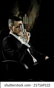 Stylish hispanic young handsome man model mobster spy hitman killer sitting in a chair holding a gun against his forehead