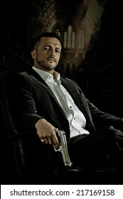 Stylish hispanic young handsome man model mobster spy hitman killer sitting in a chair holding a gun over dark background