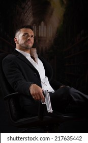 Stylish hispanic young handsome man model mobster spy hitman killer looking up sitting in a chair holding a gun over dark background