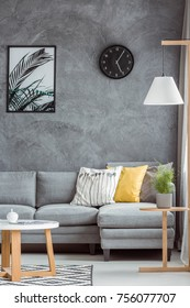 Stylish home decor with gray wall, sofa, lamp, coffee table, modern poster and decorative pillows