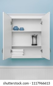 Stylish home decor on shelves of clean white cabinet, empty space for product display, light blue wall paint, white beadboard or wainscoting