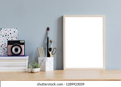 Stylish home interior with mock up photo frame on the brown wooden table with office accesories, instant camera, tillandsia in design pots, books and notes. Grey walls. Minimal concept of mockup.