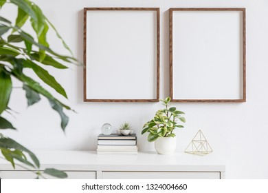 Stylish home interior with two brown wooden mock up photo frames on the white shelf with books, beautiful plants, gold pyramid and home accessories. Minimalistic concept of white room decor.