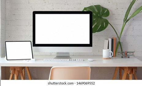 Stylish home office with blank screen desktop computer and tablet with stationery