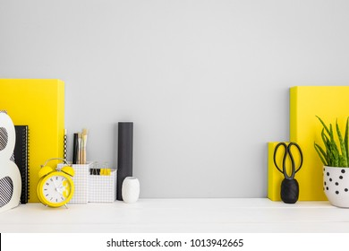 Stylish home office desk with copy space, cactus, statuette, books, and yellow office supplies. Mock up poster frame.