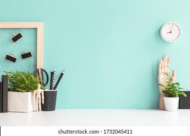 Stilvolle Arbeitsfläche im Heimbüro mit schwarzen Vorräten, Pflanzen und Kisten. Minimaler Arbeitsplatz.