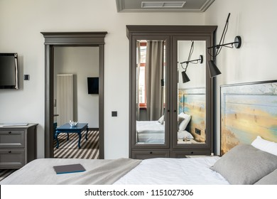 Stylish hotel room with light walls and a striped floor. There is a double bed with a colorful wooden bedhead, dark gray wardrobe with mirrors, stand, black lamps on the wall, blue table, TVs.