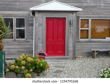 Stylish house front with weathered wood, red door and pebble garden at Eve Bay, Wellington South Coast New Zealand