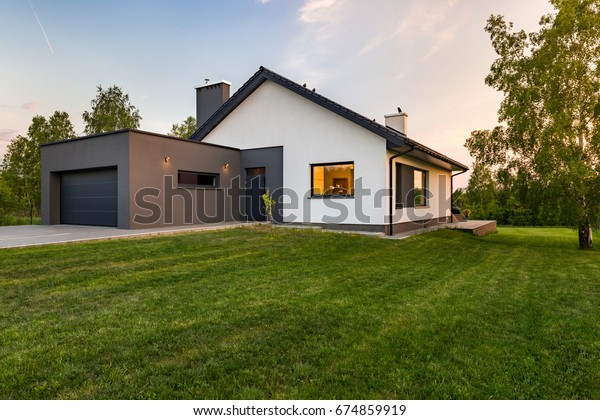 Stylish house with large lawn and garage, outdoors