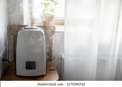 Stylish humidifier near the window. Technology Humidification and air purification in the square.