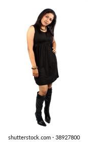 A stylish Indian babe in a black glamorous dress, posing on white studio background.