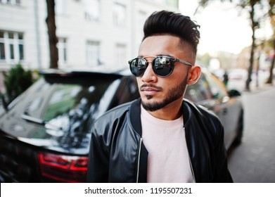 Stylish indian beard man at black leather jacket and sunglasses against business suv car. India model posed outdoor at streets of city.