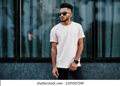 Stylish indian beard man at pink t-shirt, sunglasses. India model posed outdoor at streets of city.