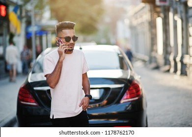 Stylish indian beard man at sunglasses and pink t-shirt against luxury car and speaking on mobile phone. India rich model posed outdoor at streets of city.