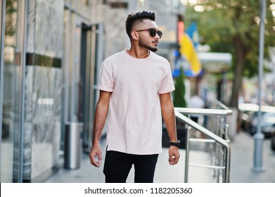 Stylish indian beard man at sunglasses and pink t-shirt. India model posed outdoor at streets of city.