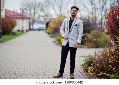 Stylish indian man with bindi on forehead and glasses, wear on suit posed outdoor.