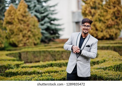 Stylish indian man with bindi on forehead and glasses, wear on suit posed outdoor against green bushes at park and looking at his watches.