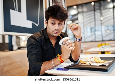 Stylish indian man sitting at fast food cafe and drink soda.