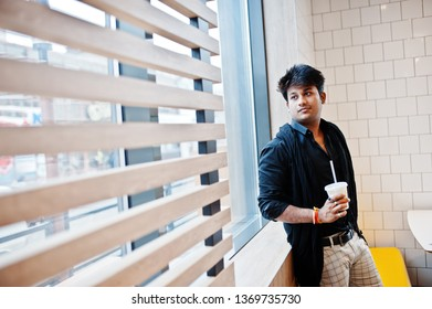 Stylish indian man stay near window with cup of coffee on fast food cafe.