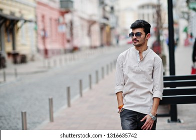 Stylish indian model man in casual clothes and sunglasses posed outdoor at street of India.
