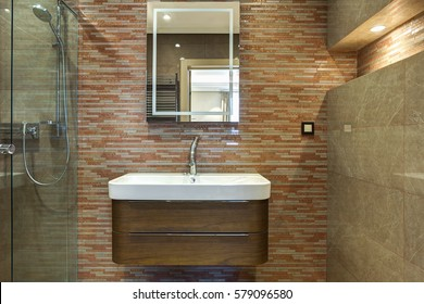 Stylish interior of bath room in modern style with square mirror and white ceramic sink with wooden cupboard under. Room in brown color.