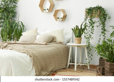 Stylish interior of bedroom with green houseplants