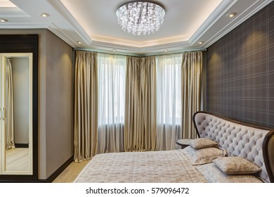 Stylish interior of empty bedroom with crystal chandelier in center of ceiling, big panoramic windows and cozy bed with. Gray wall with checked print of wallpapers. Wardrobe built into the wall.