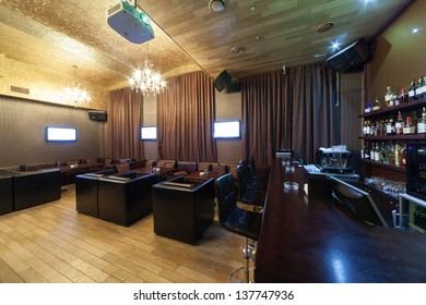 Stylish interior of karaoke bar with leather armchairs and many screens.