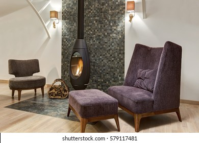 Stylish interior of living room with fireplace where fire is burning and basket with firewood near. Two armchair and little table. Room in gray, violet and white colors.