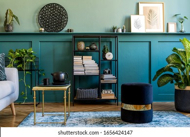 Stylish interior of living room with gray sofa, design pouf, coffee table, plants, pillow and elegant personal accessories. Wood panelling with shelf. Modern home decor. Mock up poster frame. Template