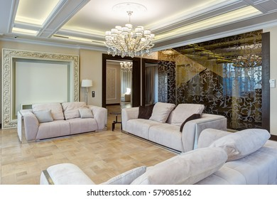 Stylish interior of living room in white, beige and brown colors. Glasses wall with pattern, three cozy sofas with pillows for big group of people. Luxury crystal chandelier in center of ceiling.