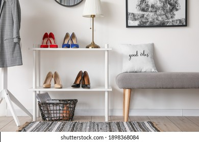 Stylish interior of modern hall with shoes on stand and bench
