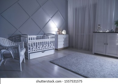 Stylish interior of room with baby bed at night